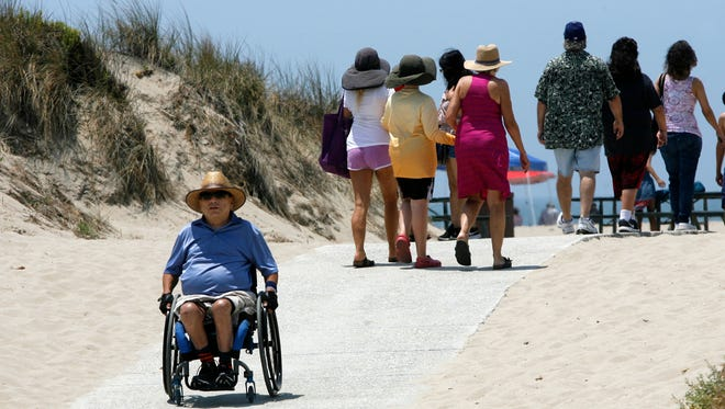 Dave Fuentes rolls down the path from Ed Hunt Rehab Point at Oxnard Beach Park during the 25th anniversary celebration of the project. Fuentes is a volunteer with the Ventura County Health Insurance Counseling Advocacy Program.