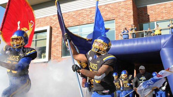 Mikey Daniel (26) carries a military flag out of the
