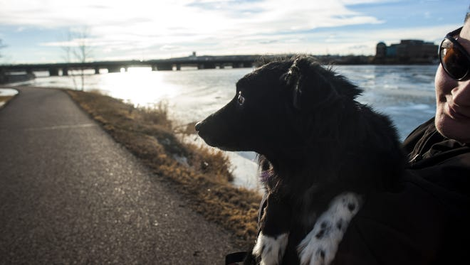 Jessica Corbett holds her dog, Bella, after finishing a walk along River's Edge Trail.