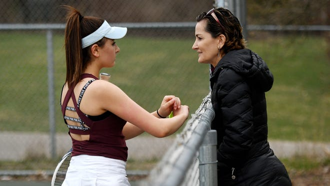 Okemos girls tennis head coach Lisa Semerly, right, talks with her daughter Yana during her number four singles match against Grand Ledge on Tuesday, April 24, 2018, at Grand Ledge High School.
