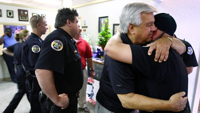 West Memphis Chief of Police Bob Paudert is comforted on May 24, 2010, by his officers as he joins the entire force for roll call for the first time since his son, Sgt. Brandon Paudert, and officer Bill Evans where gunned down during a routine traffic stop.