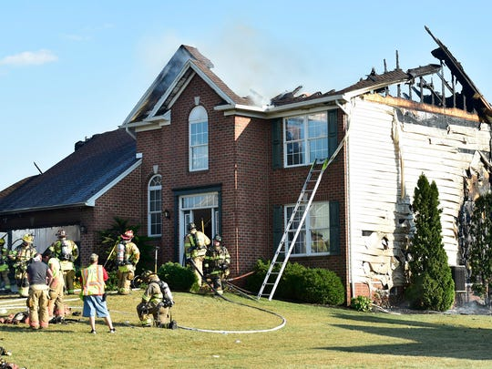 Firefighters extinguish a blaze at a home the caught fire Tuesday, September 6, 2016 at 13142 Whispering Spring Drive, Antrim Township. The family was not home when the fire started and there were no injuries, according to Rescue Hose Fire Chief Kevin Barnes.