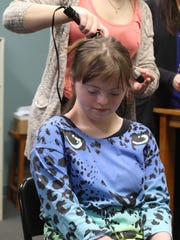 Jess Slough, 16, seated, waits patiently as a hair stylist curls her hair for Friday's Night to Shine prom hosted by 2/42 Church in Brighton.