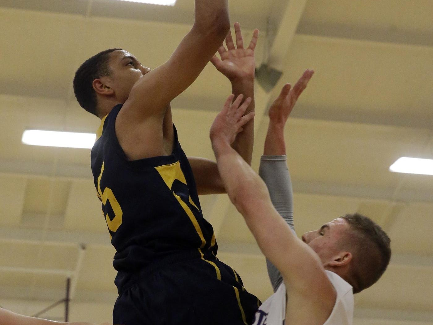 Walnut Hills forward Omari Peek drives to the basket for the Eagles in a game with Glen Este last season.