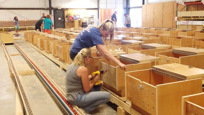 Volunteers from Fellowship Bible Church worked to assemble 102 lockers this weekend for Lane College's football team on Saturday.