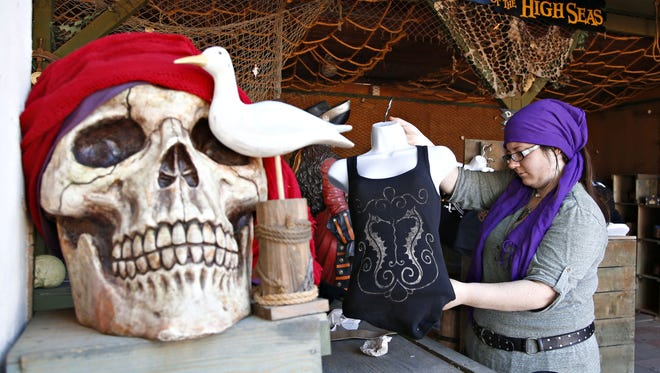 Amanda Turner, a sales associate at Treasures of the High Seas, prepares a display for the opening of the Renaissance Festival in Gold Canyon on February 5, 2016.