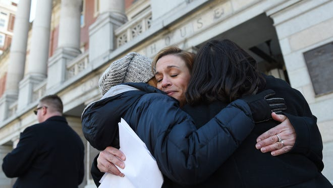 Kelsey Lauder, left, and Maggie Holroyd, right, the organizers for the March For Our Lives rally, embrace Chera Gardinier Stough, a former Red Lion Area Junior High teacher, after she spoke at the rally in downtown York on Saturday