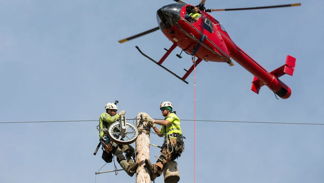 Vectren workers, Jason Wright and Nate Ruebke, install fiber optic wire on Posey County transmission lines via helicopter on Tuesday morning. The work is expected to last through mid-November.