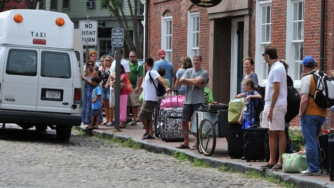 Visitors line up for taxi service along Main Street on Nantucket. Amid the pandemic, the town waived the requirement that taxi license holders must operate during the summer. As a result, only a fraction of cabs were on the road this high season compared with years past, and those still driving have sometimes been overwhelmed by the demand.