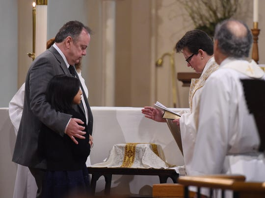 Matthew McNamara and daughter Roxanne reflect over the urn of Tracy Hermann as Reverend Susan Fortunato prays during his funeral service at Christ Episcopal Church in the City of Poughkeepsie on Wednesday.  McNamara and Hermann married in 2004 and adopted Roxanne in 2006. Hermann passed away from a heart attack on March 3rd.