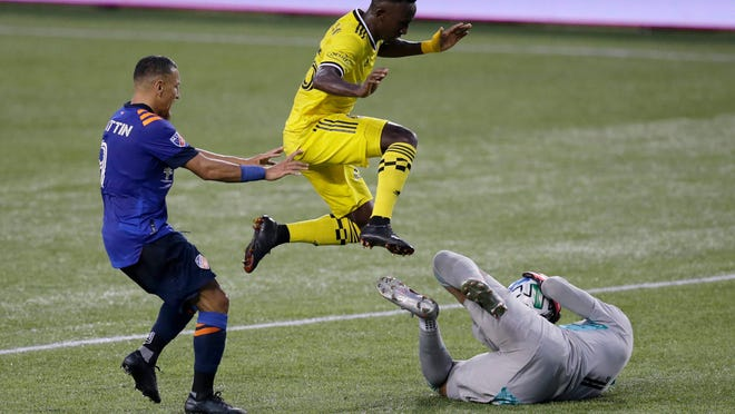 Columbus Crew defender Harrison Afful (25) leaps over C Cincinnati Eloy Room goalkeeper (1) as he makes a stop in the first half of the annual Hell is Real Derby between the two MLS teams  at Nippert Stadium in Cincinnati on Saturday, Aug. 29, 2020. The game ended in a 0-0 tie.