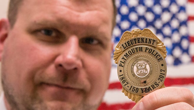 Plymouth Detective Lt. Jamie Grabowski holds his badge commemorating the city's 150th anniversary.