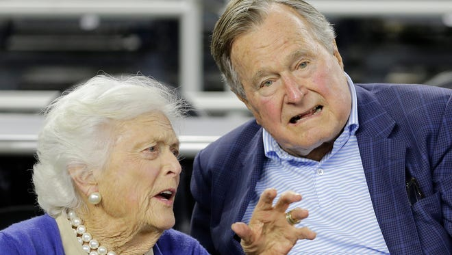 Former President George H.W. Bush and his wife Barbara Bush speak before the first half of a college basketball regional final game between Gonzaga and Duke, in the NCAA Tournament Sunday, March 29, 2015, in Houston. (AP Photo/David J. Phillip)