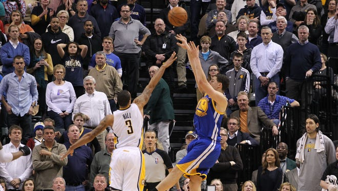 Golden State Warriors guard Klay Thompson, right, makes the winning basket with .06 of a second on the clock against Indiana Pacers guard George Hill (3) at Bankers Life Fieldhouse.