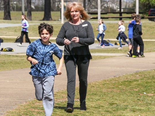 Nathan Johnson, 8, left, a second-grade student at Centerville Elementary, runs by his teacher Teresa Sanders, right, Monday at the Centerville Elementary School running club in Anderson.