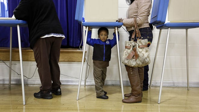 A woman brings her son with her while she casts a ballot at Brandies Elementary in 2012.
