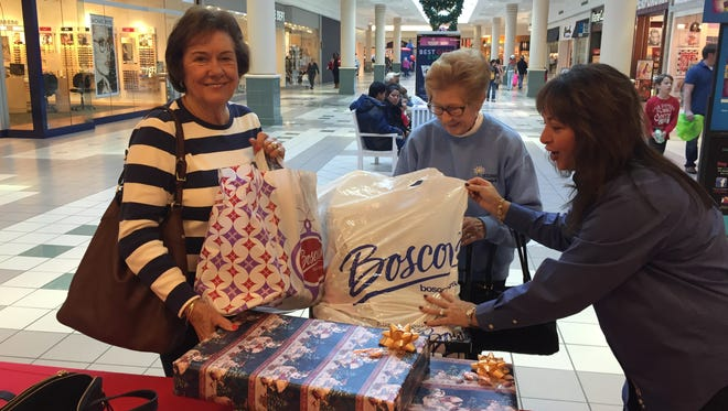 Edie Wallace, (left) and Kathy Randle, both of Cape May, are helped by Daily Journal Advertising Manager Robin Adams after having their gifts wrapped during a Boscov's charity fundraiser on Saturday.