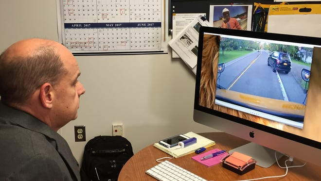 Chenango Forks Superintendent of Schools Joe Peck watches a video of an SUV passing a stopped school bus, nearly hitting a student.