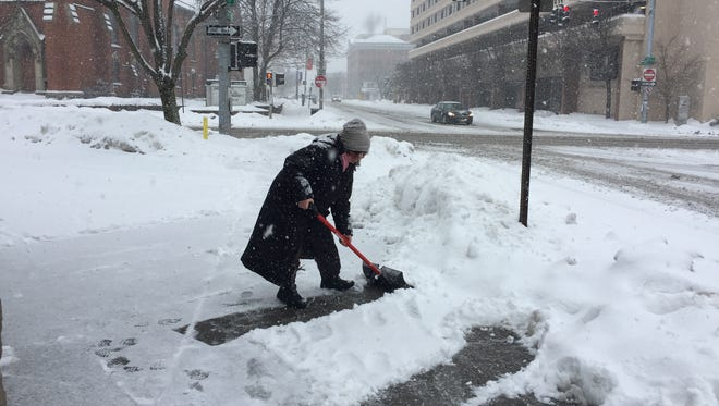 Laura Forman, a tax preparer with H&R Block in Poughkeepsie, shovels the sidewalk in front of the business.