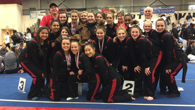 Canton's varsity girls gymnastics team celebrates after winning the MHSAA team regional championship Saturday at Plymouth High School.