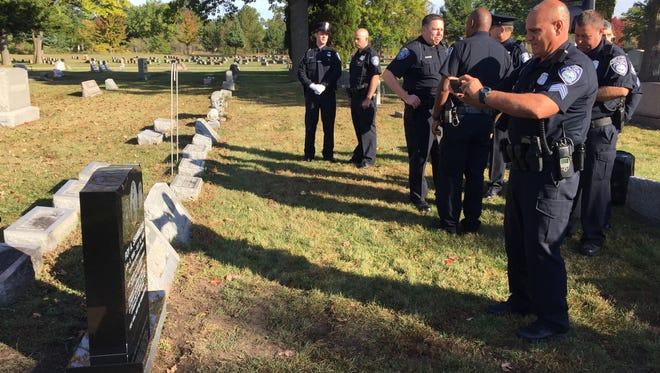 Port Huron Police Sgt. David Seghi takes a photo of a new headstone honoring Detective Sgt. Roy Shambleau, who was killed in the line of duty. Seghi has retired after more than 25 years as a Port Huron police officer