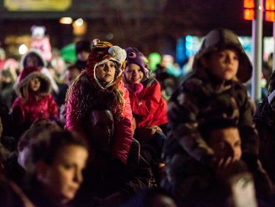 Children watch as Santa prepares to light the Christmas