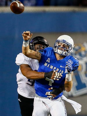 University of Memphis quarterback Riley Ferguson (right) throws an interception after being hit by University of Tulsa defender Jeremy Smith (left)  during second quarter action at the Liberty Bowl Memorial Stadium.