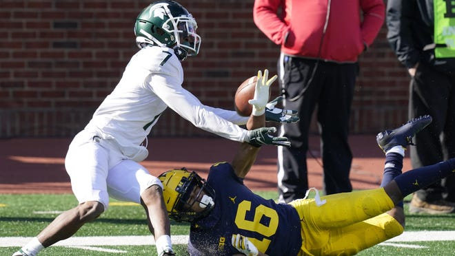 Michigan State wide receiver Ricky White (7) makes a catch while defended by Michigan defensive back Jalen Perry (16) during the second half of an NCAA college football game, Saturday, Oct. 31, 2020, in Ann Arbor, Mich.