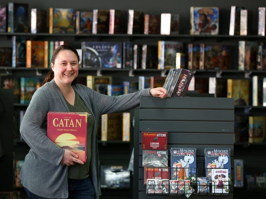 Camille Jones, the co-owner of Borderlands Games, holds popular board game Settlers of Catan inside the shop.