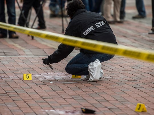 A Burlington police investigator removes a knife from