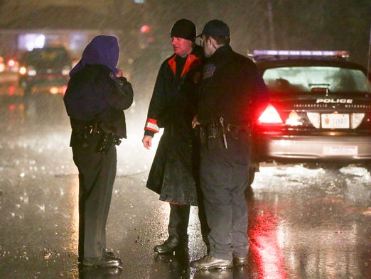Indianapolis police officers talk during a rain storm at the scene where four people were reportedly shot on the south side, 3400 South Parker, Thursday, February 19, 2014.