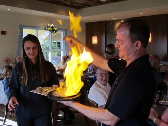 "Owner Tony Bekurti serves his popular saganaki Greek cheese appetizer that is set ablaze tableside with a little ouzo and a big ""Opa!"" at VillageWalk Bar & Grill in Bonita Springs."
