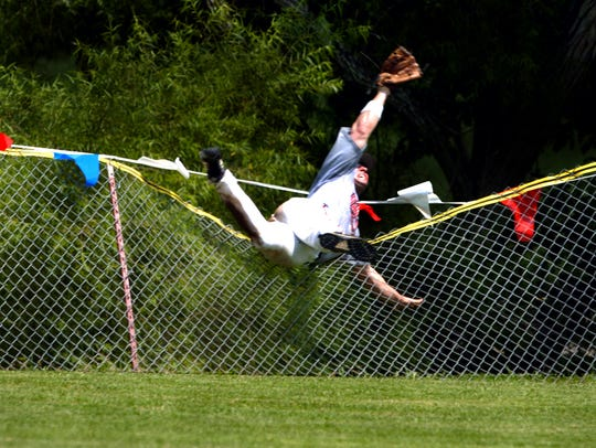 Jason Kendrick of the Dan Smith softball team dives over the fence.
