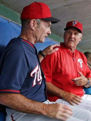 Minnesota Twins manager Paul Molitor, left, and Philadelphia Phillies manager Ryne Sandberg (23) chat in the dugout after talking with reporters before a spring training baseball game between their two teams in Clearwater, Fla., Monday, March 23, 2015. Both are Hall of Famers. (AP Photo/Kathy Willens)