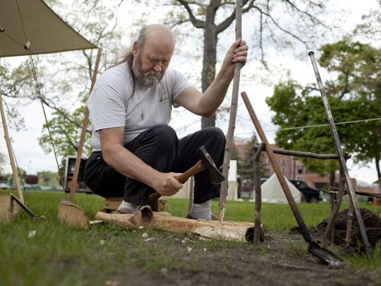James Snellenberger of East Lansing uses a tomahawk to make stakes.