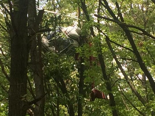 A helicopter being used to inspect high-voltage lines crashed in some Caledonia-area trees on May 29, 2015.