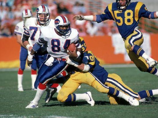 Tight end Buster Barnett (84) of the Buffalo Bills tries to break away from a tackle as linebacker Mel Owens (58) of the Los Angeles Rams closes on him from behind during a game at Anaheim Stadium on Nov. 27, 1983, in Anaheim, California. The Rams won 41-17.