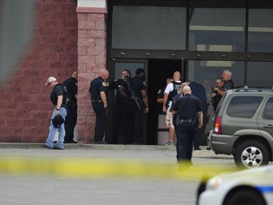 Police officers and fire personnel work on the scene of a reported shooting at a movie theater in Tennessee.