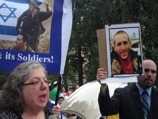Rhoda Cohen, right, of East Brunswick speaks at rally on Wednesday in Highland Park co-organized by Josh Fine, left, of Highland Park. Fine is holding a photo of Cohen's nephew, a soldier with the Israel Defense Force who was killed in battle on July 21.