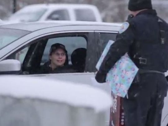 Lowell police officer Scot VanSolkema hands out presents to drivers.