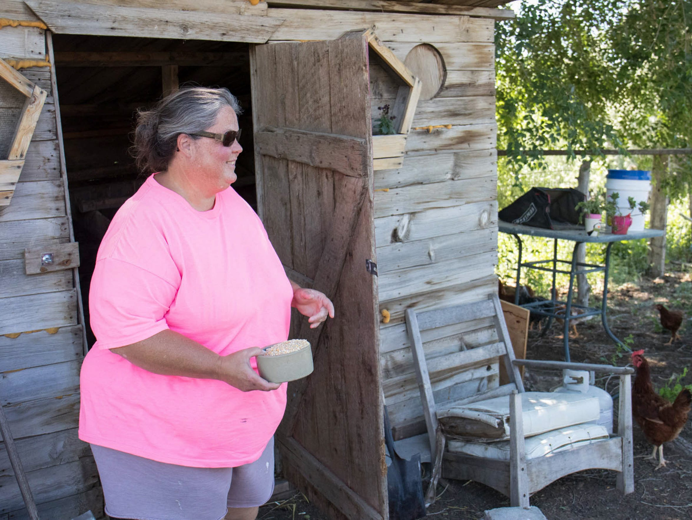 Leslie Rendon (left) feeds her chickens and Kathleen