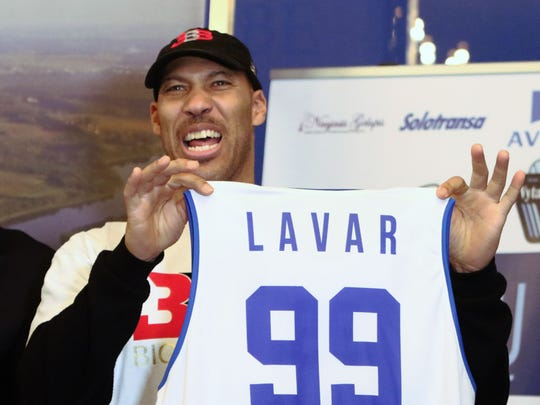 LaVar Ball holds up a jersey during a press conference