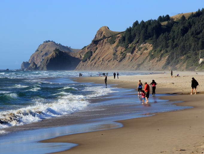 A hike at Roads End State Recreation Site takes visitors along a beautiful stretch of beach toward the large Cascade Headland in the distance.