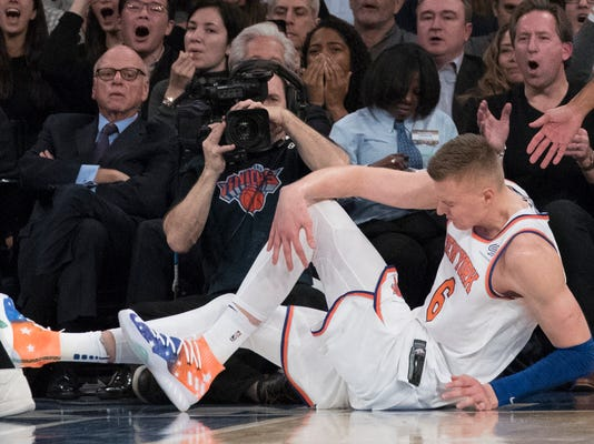 New York Knicks forward Kristaps Porzingis clutches his knee after a fall during the first half of the team's NBA basketball game against the Milwaukee Bucks, Tuesday, Feb. 6, 2018, at Madison Square Garden in New York. (AP Photo/Mary Altaffer)