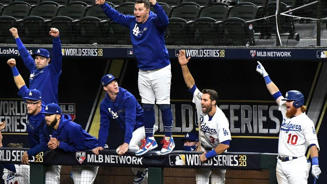 The Los Angeles Dodgers dugout celebrates a solo home run by Mookie Betts in the sixth inning against the Tampa Bay Rays in Game 1 of the World Series at Globe Life Field in Arlington, Texas, on Tuesday, Oct. 20, 2020. The Dodgers won, 8-3.