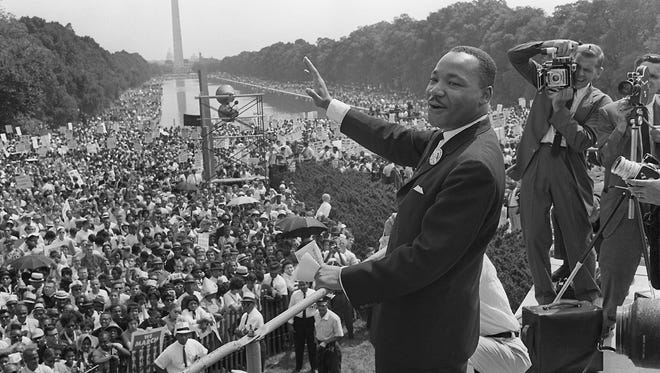 Civil rights leader Dr. Martin Luther King Jr., center, waves to supporters on August 28, 1963, during the March on Washington at the National Mall in Washington, D.C.