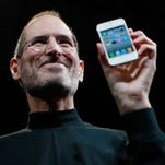 In this June 7, 2010, file photo, Apple CEO Steve Jobs holds a new iPhone at the Apple Worldwide Developers Conference in San Francisco.