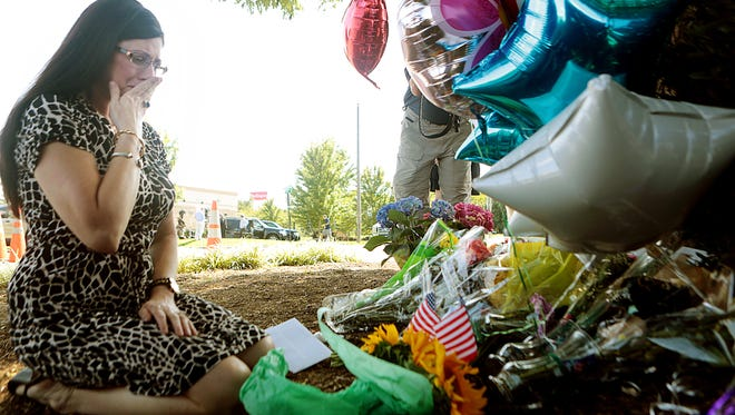 Pamela Cook, of Roanoke, Va., delivers flowers to WDBJ's Digital Broadcast Center after hearing news of a shooting involving two of the news team members, in Roanoke, Va., Wednesday, Aug. 26, 2015. A WDBJ- TV reporter and cameraman were shot to death during a live television interview Wednesday by a gunman who recorded himself carrying out the killings and posted the video on social media after fleeing the scene. (Heather Rousseau/The Roanoke Times via AP) LOCAL TELEVISION OUT; SALEM TIMES REGISTER OUT; FINCASTLE HERALD OUT;  CHRISTIANBURG NEWS MESSENGER OUT; RADFORD NEWS JOURNAL OUT; ROANOKE STAR SENTINEL OUT; MANDATORY CREDIT