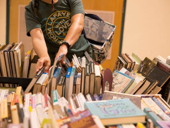 A shopper looks through books during the Friends of