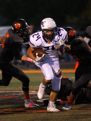 Kirtland Central's Jacob Franco carries the ball against Aztec on Friday at Fred Cook Memorial Stadium in Aztec.